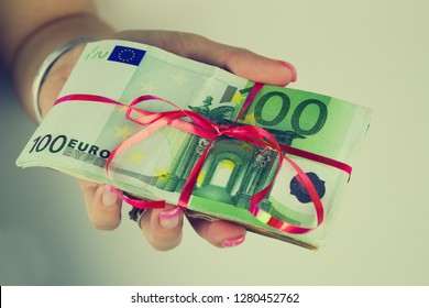 A woman holds a 100 euro banknote package.Package of euro banknotes tied with ribbon. Woman with sexy nails  holds banknotes.