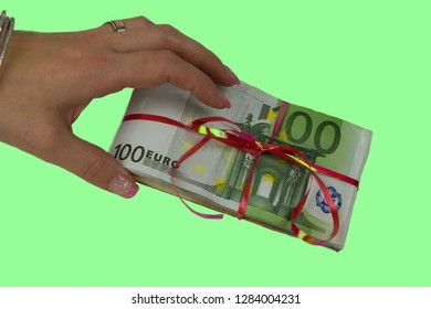 A woman holds a 100 euro banknote package on green background.Package of euro banknotes tied with ribbon. Woman with sexy nails  holds banknotes.