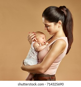 A woman holds a baby in her arms. After feeding. Colorful background.