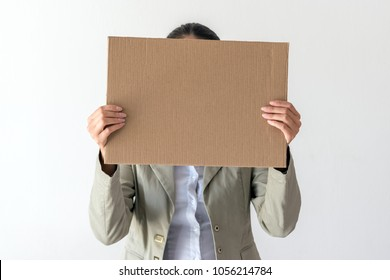 A woman holds blank sign in front her face on white background.