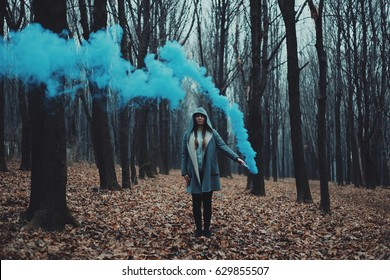 Woman holds up blue smoke flare to signal for help in the middle of nature. Rainy forest in mist.