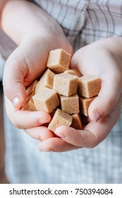 woman holds brown sugar cubes in hands