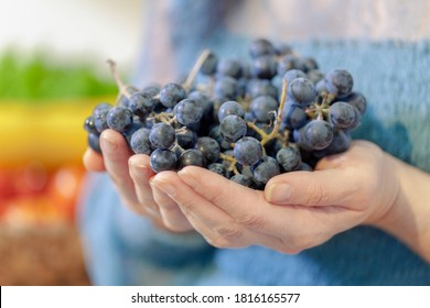 Woman holds bunches of grapes in her hands