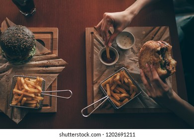 Woman holds burger with potato fries on background in cafe. Tasty grilled burgers with beef, tomato, cheese, cucumber and lettuce. People and eating concept. Top view. American food. Toned image.