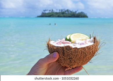 Woman holds Ceviche Dish served in a coconut shell against a islet in Muri lagoon Rarotonga, Cook Islandss. Food background and texture. Copy space