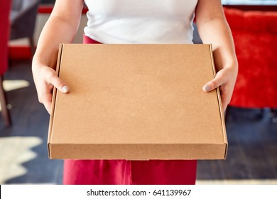 Woman holds closed box with pizza