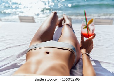 Woman holds a cocktail, while taking a sunbathe on sunbed, on the beach, near the sea. Close-up view.