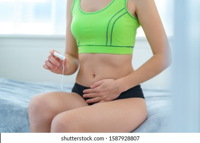 Woman holds cotton female hygienic tampon for protection from bleeding during menstruation. Menstrual hygiene and intimate care. Pain during painful menses period and pms