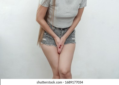 Woman holds crotch with her hands, she wants to urinate - concept of urinary incontinence, gynecological problems