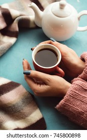 Woman holds cup of warm tea on the blue background. Delights of the fall. Disease prevention