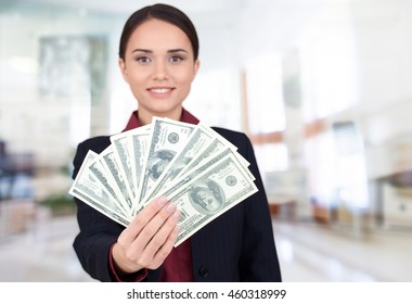 Woman holds currency.