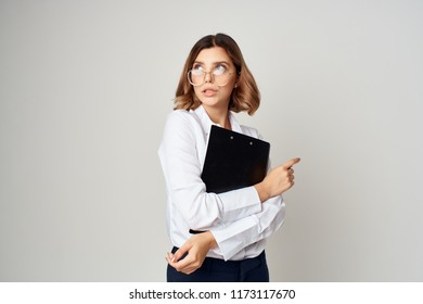 woman holds documents in her hands and looks aside