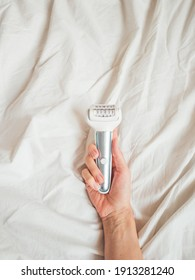 Woman holds epilator on crumpled bed background. Epilation cosmetological procedure for hair removal. Spa at home. Skin care.