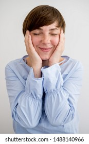 Woman holds face with hands and closed her eyes from pleasure
