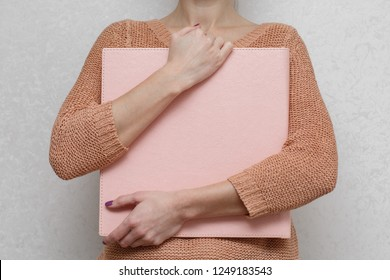 a woman holds a family photobook the person looks at the photo book sample pink photo album  wedding photoalbum with  leather cover.
