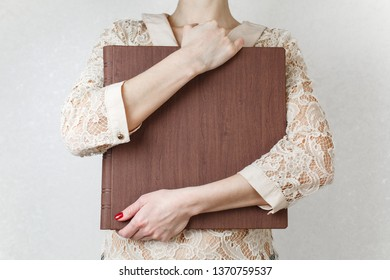 a woman holds a family photobook the person looks at the photo book sample brown  photo album  wedding photoalbum with  leather cover.