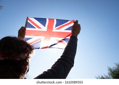 Woman holds the flag of Great Britain against the sun at a patriotic moment.