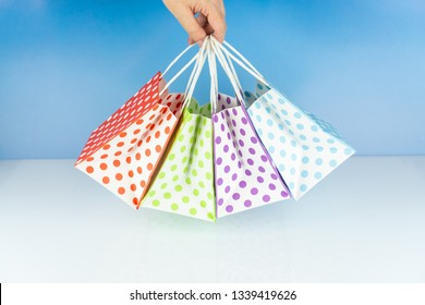 Woman holds four colorful dotted paper bags in her hand, blue background and copy space