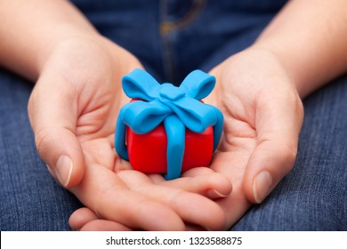 Woman holds gift wrapped with blue ribbon. Gift box and ribbon are made out of play clay (plasticine).