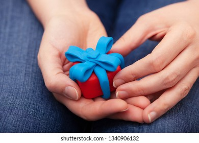 Woman holds gift wrapped with blue ribbon. Gift box and ribbon are made out of play clay (plasticine). Close up.