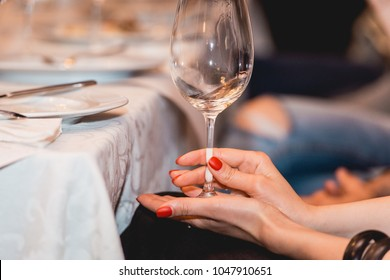woman holds glass of red wine. people consider the color of the wine and try how it smells in different glasses