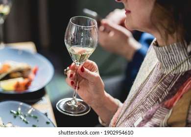 woman holds glass of white wine. people consider the color of the wine and try how it smells in different glasses