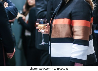 A woman holds a glass of wine at a corporate networking event in Washington, D.C.