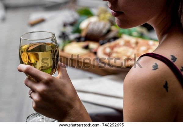 Woman holds glass of wine, pizza in background