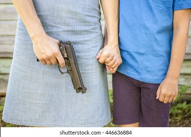 Woman holds the gun, nearby there is a the boy whom she strongly holding his hand, outdoors