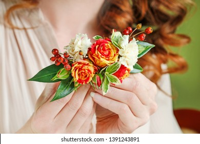 Woman holds a hair clip with fresh flowers - roses and carnations.