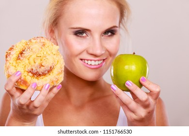 Woman holds in hand cake sweet bun and apple fruit choosing, trying to resist temptation, make the right dietary choice. Weight loss diet dilemma concept.