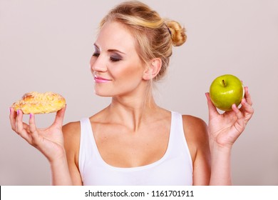 Woman holds in hand cake sweet bun and apple fruit choosing, trying to resist temptation, make the right dietary choice. Weight loss diet dilemma gluttony concept.