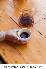 woman holds in hand a ceramic mug with black coffee. alternative brewing of specialty coffee. background light wood
