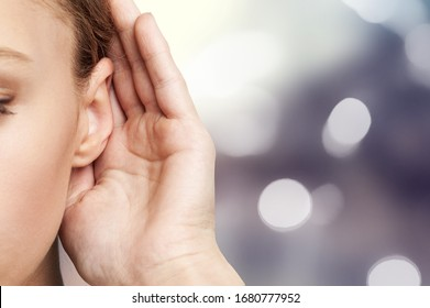 A woman holds hand near her ear and listening to something