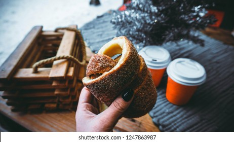 Woman holds in hand Trdlo or Trdelnik, it is a national street street food of Prague on the background of wooden table with glasses of mulled wine