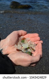 A woman holds a handful of beach glass at a beach.