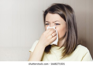 woman holds handkerchief, napkin in her hand. runny nose, common cold, virus