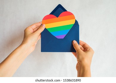 Woman holds in hands envelope and heart in the colors of the rainbow. Young beautiful girl. LGBT pride month. Coming out. Lesbian Gay Bisexual Transgender. LGBTQ+ flag. Love, human rights, tolerance