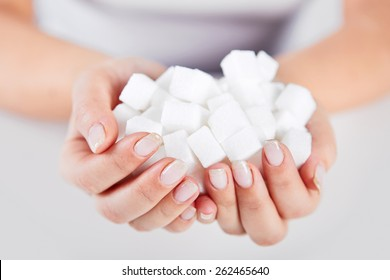 Woman holds in hands of a handful of sugar cubes