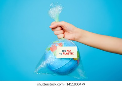 Woman holds in hands plastic bag and planet earth with text sticker-SAY NO TO PLASTIC at blue background. The concept of plastic pollution.