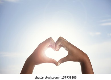 Woman holds hands up to sky in the shape of a heart around the sun.