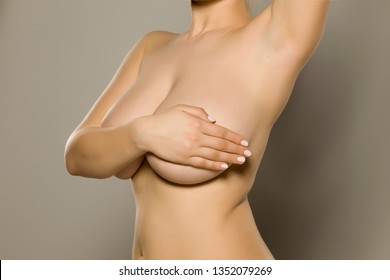 Woman holds her big breasts with her hand on gray background