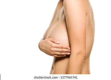Woman holds her big breasts with her hand on white background