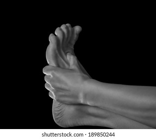 Woman holds her foot, pain in the foot, monochrome image