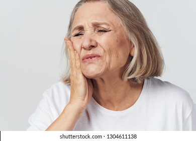 A woman holds her hand near the face with a toothache