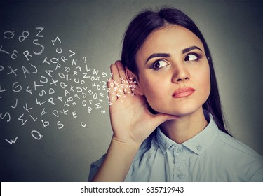 Woman holds her hand near ear and listens carefully alphabet letters flying in isolated on gray wall background