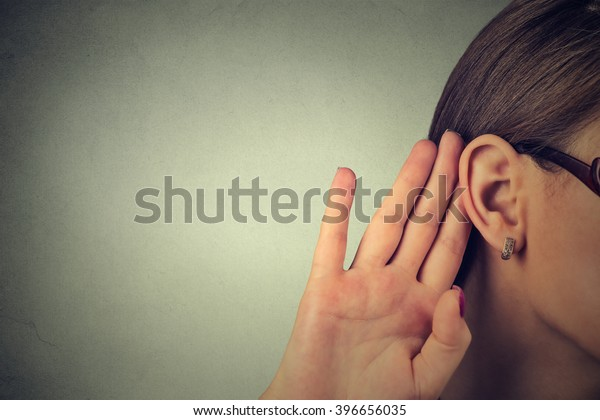 Woman holds her hand near ear and listens carefully isolated on gray wall background