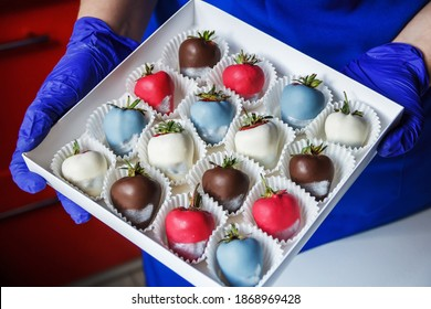 A woman holds in her hands a box of chocolate covered strawberries, dessert for Valentine's Day, romance, food as a gift. Homemade red strawberries in chocolate. A romantic dessert as a gift.