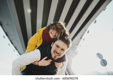 Woman holds her man tightly standing under the steel bridge