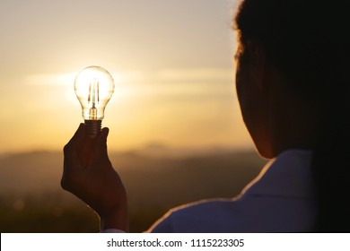 A woman holds a house light bulb in which the sun is setting inside. Concept of: renewable energy, nature, electricity, love for the environment and for the planet.